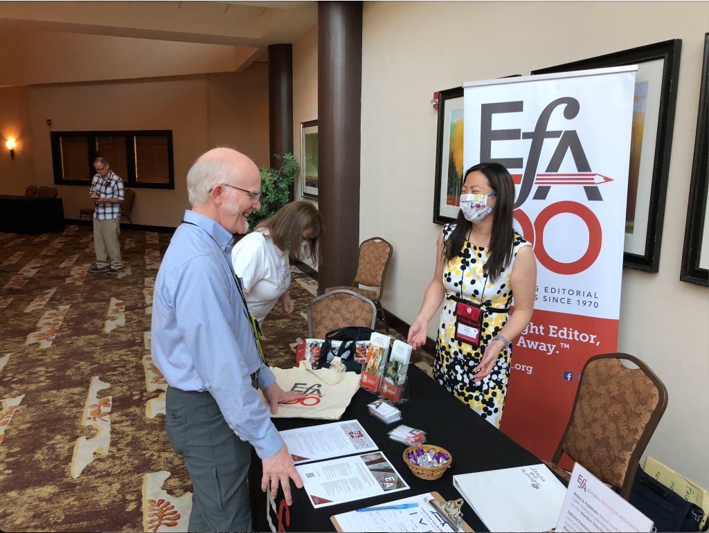 John Olsen, past President the League of Utah Writers, visiting the EFA table staffed by booth captain Crystal Shelley and Chris Thomas in the background.