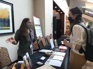 Volunteer Kristy Gilbert speaking with a booth visitor