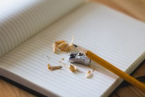 sharpened pencil and wood shavings on an open notebook