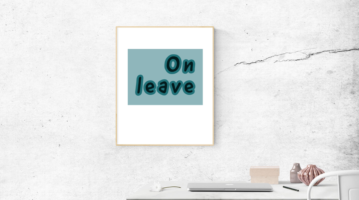 """White table with closed laptop. White wall with sign that says """"On leave."""""""